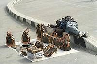 - African immigrant itinerant seller with false Vuitton bags....- venditore ambulante immigrato africano con finte borse Vuitton
