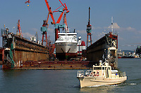 Small boat passes large ship in dry dock.