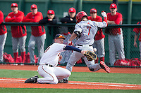Pavin Smith (10) of the Virginia Cavaliers can't handle a low throw as Trey Stover (7) of the Hartford Hawks hustles down the first base line at The Ripken Experience on February 27, 2015 in Myrtle Beach, South Carolina.  The Cavaliers defeated the Hawks 5-1.  (Brian Westerholt/Four Seam Images)