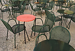 Empty cafe tables pattern design nobody sitting at restaurant tables outside. One red table all the rest green.