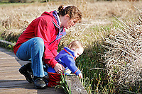 Mother and daughter on boardwalk looking over wetland, Mill Creek, Washington, USA
