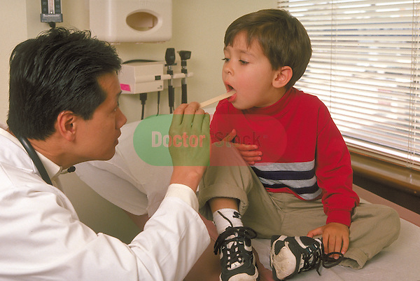 doctor examining throat of young boy sitting on examination table