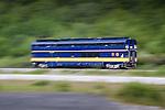 Passenger train in Alaska running by Turnagain Arm, doubledecker Chugach Explorer, caught with motion blur by panning