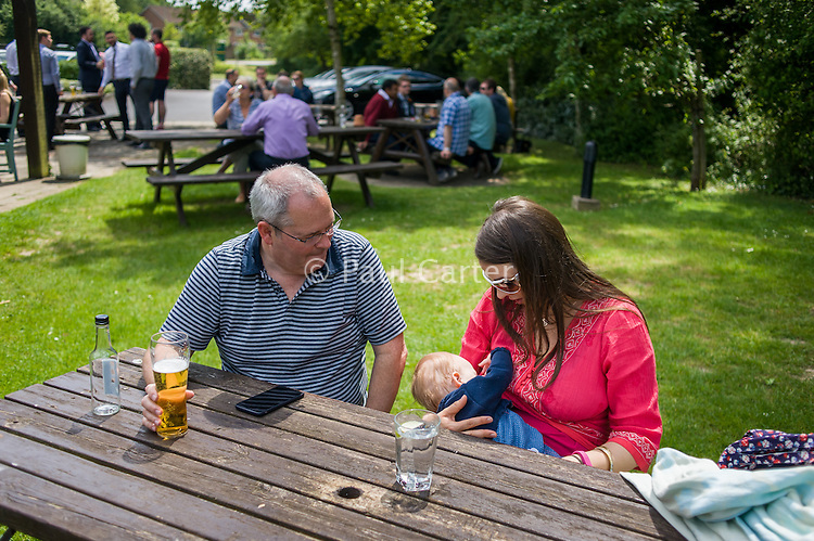 A mother breastfeeding her baby in a pub garden. Her husband is sitting beside her drinking a pint of beer.<br /> <br /> Hampshire, England, UK<br /> 19/06/2013<br /> <br /> © Paul Carter / wdiip.co.uk