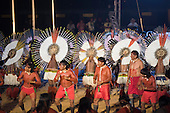 Xavante warriors dance in front of a line of Karaja participants who are wearing their distinctive wheel-shaped ceremonial feather headdresses during the opening ceremony at the first ever International Indigenous Games, in the city of Palmas, Tocantins State, Brazil. Photo © Sue Cunningham, pictures@scphotographic.com 23rd October 2015