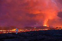a member of Hawaii County Fire Dept. tests heat protective gear next to glowing river of hot lava erupting from fissure 8 (in background) of the Kilauea Volcano east rift zone, Kapoho, Big Island, Hawaii, USA