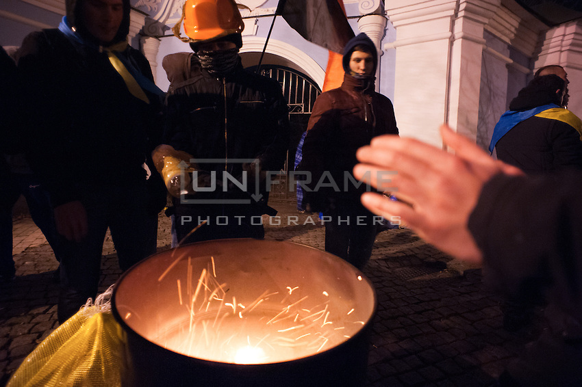 Group of young nationalists warming up during night shift.  After the violent event when crowd on Independence Square in Kiev was dispersed and more than 30 students were badly hurt, many people expressed their wish to be guards of barricades during nights.