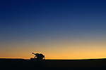 Silhouetted combine in field at sunrise getting ready to begin cutting wheat field, Eastern Washington State USA.