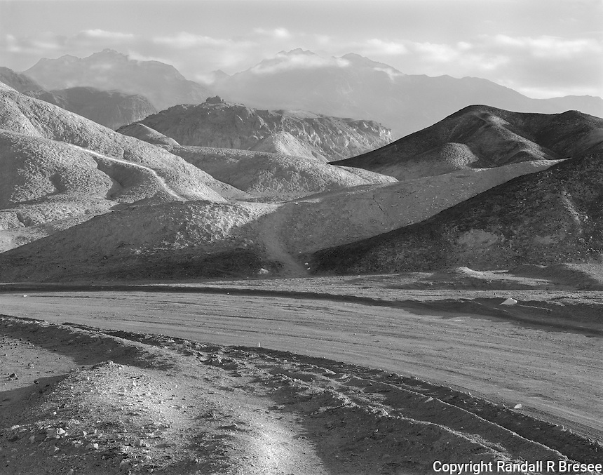 """""""Sunlight On Twenty Mule Team Road"""" <br /> Death Valley National Park, California<br /> <br /> The most dominant feature of Death Valley National Park for me is the tremendous amount of sunlight that floods the valley floor. The photo shown here was an attempt to convey this feature at one of my favorite places, Twenty Mule Team Road. The lack of plant life allows sunlight to bring soil roughness to life. I used a medium yellow filter to clear atmospheric haze a bit, darken the blue sky and strengthen shadows in the photograph. To further emphasize texture, I used a sharp f-stop on the lens and a substantial amount of lens tilt to make sure that the entire scene from foreground to distant hills was sharply focused."""