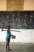 Mbati, Zambia. Boy with hand plough over his shoulder holding a book in schoolroom with blackboard with addition sums.