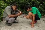 Fishing Cat (Prionailurus viverrinus) biologists, Maduranga Ranaweera and Anya Ratnayaka, investigating fishing cat scat in urban wetland, Urban Fishing Cat Project, Diyasaru Park, Colombo, Sri Lanka