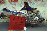 A baby girl beggar sits upon a cart in Guangzhou begging for money, the sign says that she is also for sale. An average gender inbalance 118 males to 100 females caused by the Chinese Governments One Child Policy and the  preference for boys means that there is a shortage of women in China.