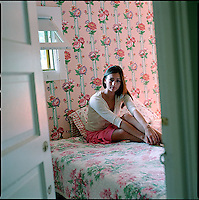 Woman sitting on bed in floral wallpapered bedroom<br />