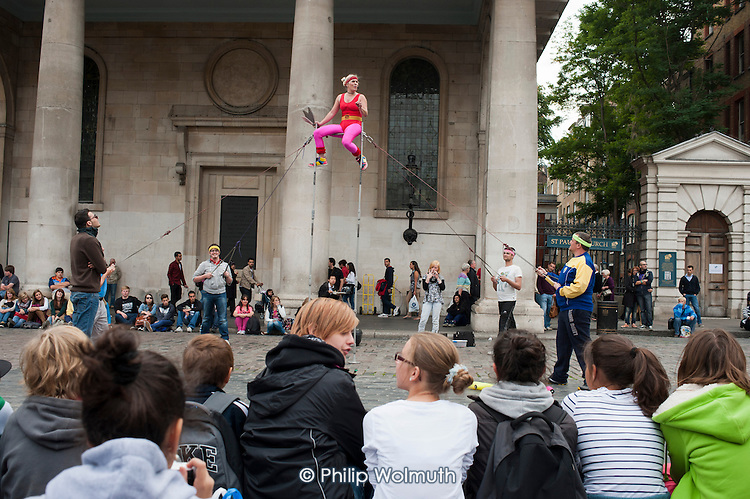 Young tourists watch a street performer in Covent Garden, London