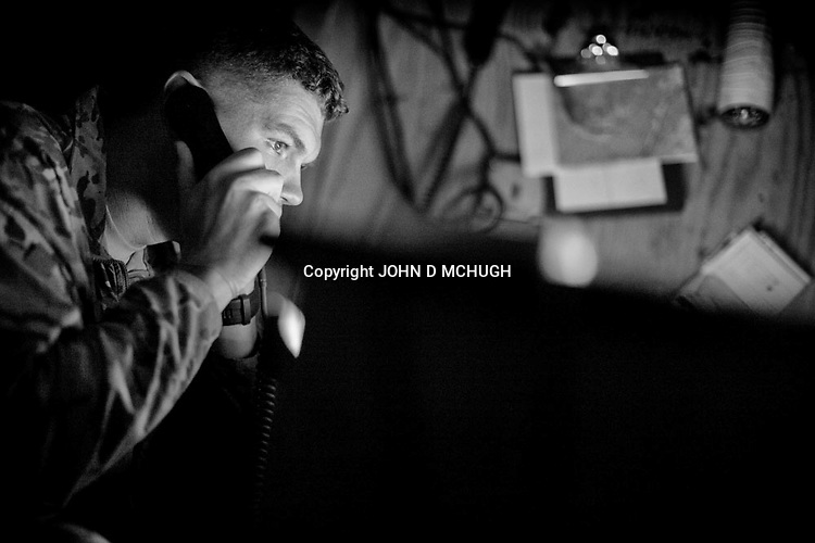 Captain Michael Brabner, Charlie Company Commander, 2/27 Infantry Regiment, 25th Infantry Division, gives orders over the radio, by torchlight, at Observation Post Mace, near Gowerdesh in northern Kunar, 18 November 2011. (John D McHugh)