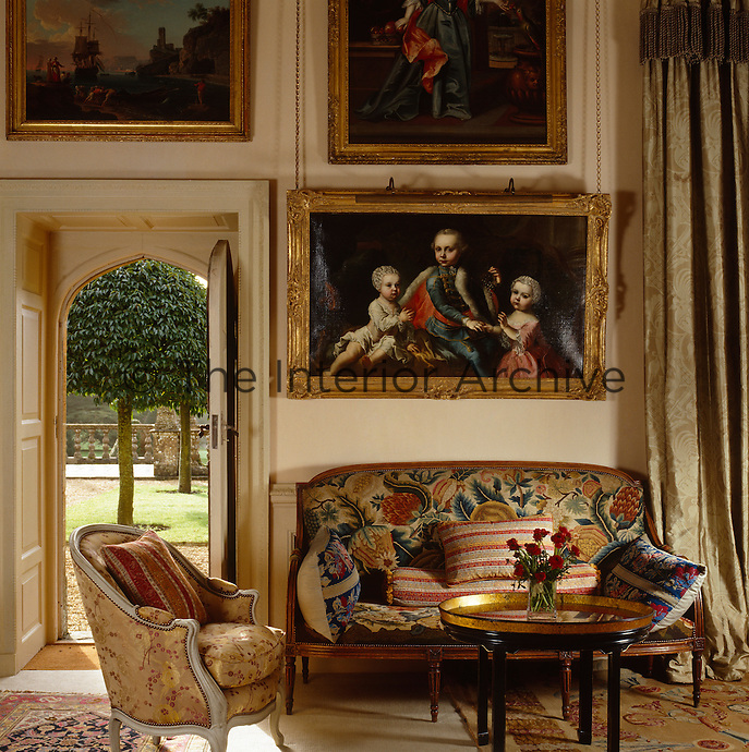 An 18th century gilt-framed portrait hangs above a sofa in the hall beside a door leading to the garden