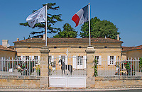 Chateau La Couspaude, the main building, with a white iron fence a French flag and a statue of a black horse in the court yard Saint Emilion Bordeaux Gironde Aquitaine France