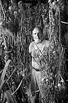 Keith Stewart amongst organic garlic hanging and drying in a barn