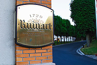 A polished brass sign saying that it is the oldest house in Champagne and the tree lined allee road leading up to the winery building, Champagne Ruinart, Reims, Champagne, Marne, Ardennes, France