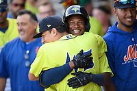 Center fielder Hansel Moreno (48) of the Columbia Fireflies, in helmet, gets a hug from Jose Butto (45) after hitting a home run in the first inning of a game against the Augusta GreenJackets on Friday, May 31, 2019, at Segra Park in Columbia, South Carolina. Augusta won, 8-6. (Tom Priddy/Four Seam Images)
