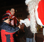 Elizabeth Bowers of Piqua watches as her son Ethan Tucker, 5, gets a candy can from Santa Claus during Christmas on the Green in downtown Piqua on Friday.