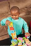 Two year old toddler boy stacking blocks making tower