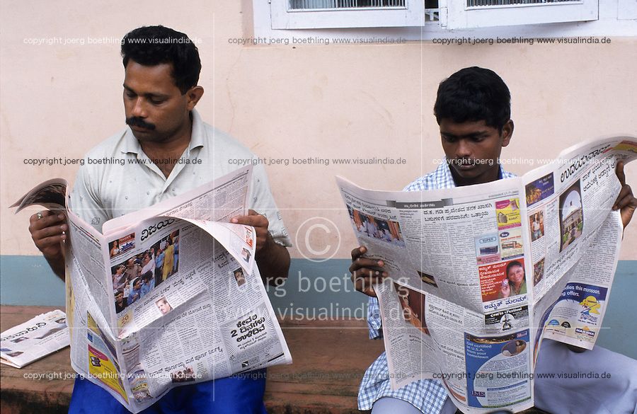 INDIA Karnataka Moodbidri, men read newspaper in Kannada language / INDIEN Maenner lesen lokale Zeitung in Kannada Sprache