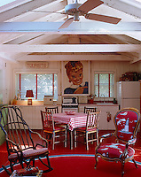 A small dining area divides the kitchen from the sitting area and the crisp red and white palette and textiles contribute to the light-hearted feel of the room