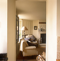The corner of a country sitting room decorated in neutral tones. A lamp stands on a round wooden table next to an armchair above which is a built-in corner cupboard.