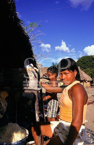 Amazon, Brazil. Koatinemo village; children using a mill to grate mandioca (manioc or cassava).