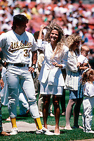 OAKLAND, CA - Jose Canseco of the Oakland Athletics and his wife Esther Canseco stand together on the field during family day before a game at the Oakland Coliseum in Oakland, California in 1990. Photo by Brad Mangin