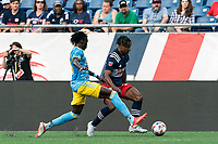 FOXBOROUGH, MA - AUGUST 8: DeJuan Jones #24 of New England Revolution dribbles down the wing as Olivier Mbaizo #15 of Philadelphia Union defends during a game between Philadelphia Union and New England Revolution at Gillette Stadium on August 8, 2021 in Foxborough, Massachusetts.