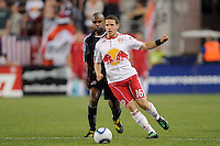 John Rooney (16) of the New York Red Bulls is defended by Didier Domi (3) of the New England Revolution. The New York Red Bulls defeated the New England Revolution 2-1 during a Major League Soccer (MLS) match at Red Bull Arena in Harrison, NJ, on June 10, 2011.