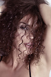 Closeup beauty face portrait of a young woman looking through her long curly brown hair with a sultry sensual look on her beautiful face Image © MaximImages, License at https://www.maximimages.com