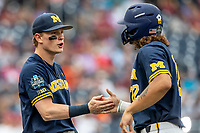 Michigan Wolverines shortstop Jack Blomgren (2) shakes hands with outfielder Jordan Brewer (22) before Game 6 of the NCAA College World Series against the Florida State Seminoles on June 17, 2019 at TD Ameritrade Park in Omaha, Nebraska. Michigan defeated Florida State 2-0. (Andrew Woolley/Four Seam Images)