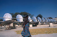 INDIA, Rajasthan, woman walking in front of parabolic mirror of worlds largest solar cooker at Brahma Kumari Ashram in Mt. Abu, the unit produce steam with sunlight which is used in the ashram kitchen to prepare 20.000 meals a day / INDIEN Rajasthan, Frau vor Parabolspiegel des weltgroessten Solarkochers im Brahma Kumari Ashram in Mt. Abu