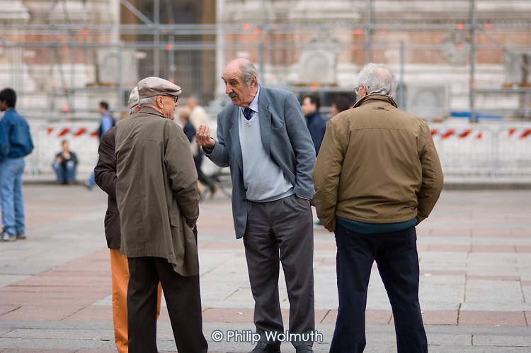Elderly men talk in the Piazza Maggiore in the centre of Bologna