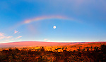 A full moon sets under an arching rainbow over Hawaii's Mauna Loa volcano. Mauna Loa is the largest voacano on earth. The volcano has been erupting for about 700,000 years and its most recent eruption occured in 1984.