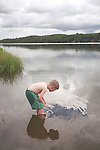 Six year old boy looking into the shallow water while wading in Echo Lake at Aroostook State Park, Maine, USA