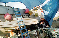 A female deckhand mends a net in the PAF boat yard in Dillingham, Alaska in Bristol Bay during the summer of 1997.