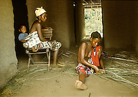 Women of Kpelle tribe socializing inside hut, young one at right weaving mat, woman at left carrying baby strapped on her back, Liberia, West Africa