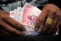 A Chinese vendor checking Renminbi notes at a wholesale market in Beijing, China..