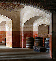 "A fine art architecture abstract of brick arches and wooden barrels with an old metal chest. Brick walls are off-white and faded red.  Afternoon shadows create horizontal patterns across the floor.  The abstract evokes historic American military buildings of the 1800's.  This image pairs well with ""Old Military Wheel and Arches."""