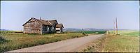 Abandoned farmhouse along dirt road<br />