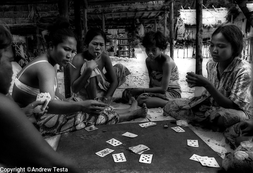 Moken women playing cards and smoking cigarettes. Scientists studying the Moken point to these kinds of activities as evidence of the detrimental effect contact with developed world is having on the Moken.