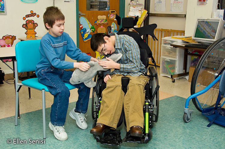 MR / Albany, NY.Langan School at Center for Disability Services .Ungraded private school which serves individuals with multiple disabilities.Boy lets classmate touch his favorite stuffed animal. Boy on the right: 11, cerebral palsy, expressive and receptive language delays; Boy on left: 10, Duchenne muscular dystrophy, expressive and receptive language delays.MR: Bro12, Bud2.© Ellen B. Senisi
