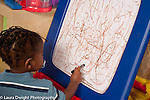 17 month old toddler boy scribbling with marker on easel