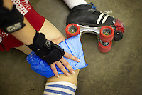 A skater ices her knee after a crash during a roller derby practice in Wilmington, Massachusetts. Roller derby is an American contact sport, popular with young women, which combines both athleticism and a satirical punk third-wave feminism aesthetic.
