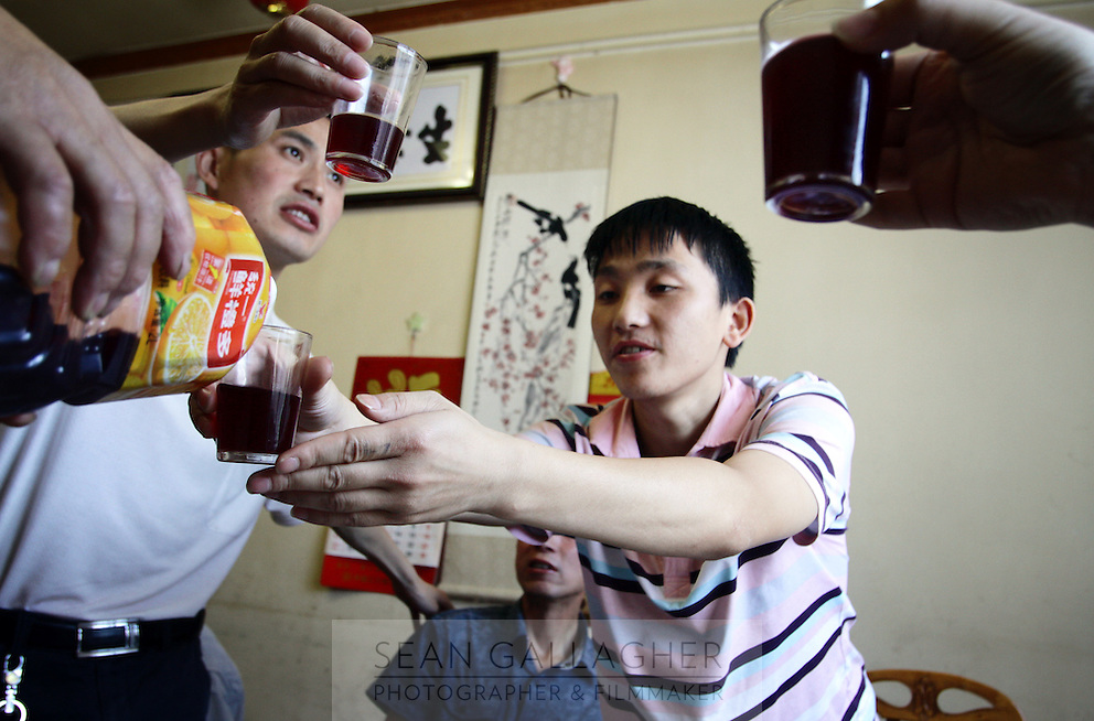 Local men toast one another during a lunch. The red alcohol which they consume is a home-brewed 'moonshine' made from a traditional Chinese medicinal plant called wuweizi that is harvested from local forests. These men claim that consumption of alcohol is good for the stomach and liver. Pingwu County in Sichuan Province, south-west China.