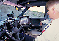 Speed camera operator in police car monitors computer that records speeder on film, law enforcement, speeding. Commerce City Colorado USA.